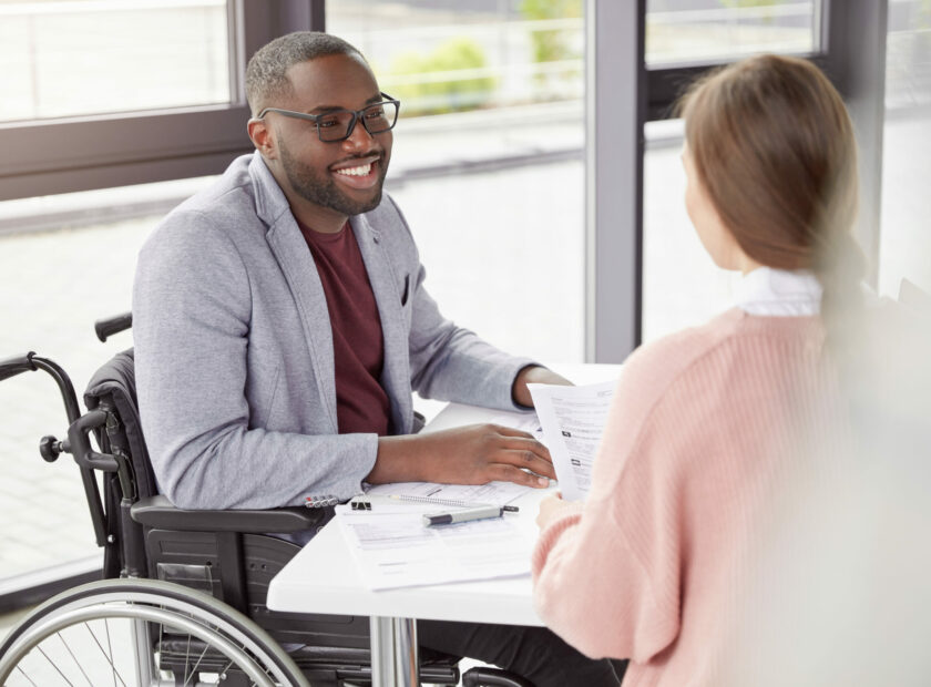 Portrait of male invalid who can`t go, sits in wheelchair, being paralysed, still work in his own comapy as director, gives commands and instruction to female secretary, happy to recieve high profit