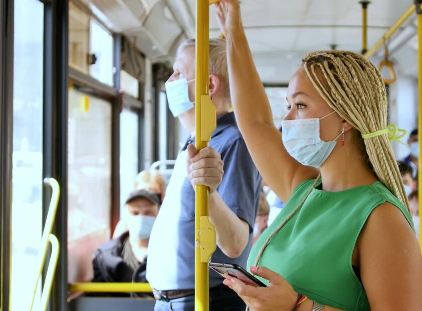 Coronavirus, covid -19, young woman with respiratory mask traveling in the public transport by bus