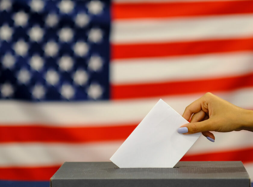 woman putting a ballot in a ballot box on election day. Close up of hand with white votes paper on usa flag background.