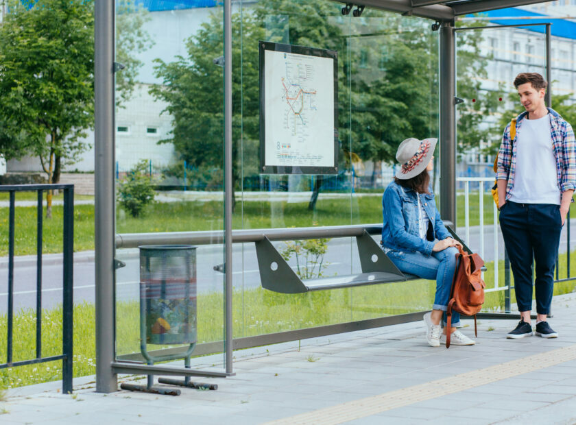 Couple communicating while waiting at bus stop. Hansome man and elegant woman with backpacks meets and talks at tram stop, outdoor. Students waiting for tram.